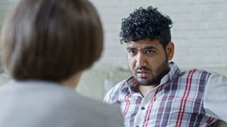 Zoom on of face of sad Arab man with beard talking to unrecognizable female psychotherapist during session