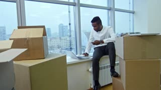 Zoom out of african american businessman sitting on window sill in new office with stacks of cardboard boxes, working on laptop and texting on smartphone