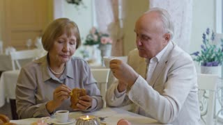 Zoom out of elderly couple relaxing in cafe: loving senior woman giving piece of pastry to affectionate husband and laughing as he kissing her cheek
