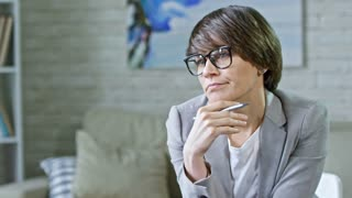 Zoom out of serious female psychiatrist in glasses talking and listening to male patient sharing feeling during session