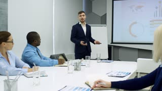 Zoom out of young businessman explaining presentation projected on whiteboard to multiethnic colleagues at office meeting