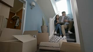 Zoom out shot of young Asian couple sitting on staircase of their new house and looking through folder with interior design ideas and layout plan