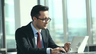 Waist up shot of white collar worker sitting at the office desk and expressing positive reaction to information on laptop screen