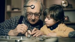 Watchmaker mending watch, his grandchild watching his work