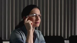 Woman at the office swiping side of smart glasses