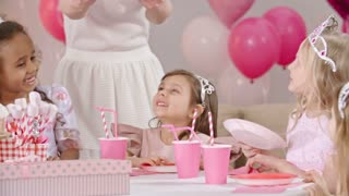 Woman putting birthday cake on table and little girls dressed like princesses blowing out candle on it and smiling