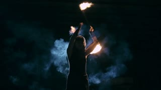 Woman standing in cloud of smoke in the darkness and rotating burning torch behind her back in slow motion
