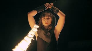 Woman standing with raised arms and twirling pair of fire chains around her body in the darkness