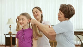 Women of different age braiding the hair of a little cutie