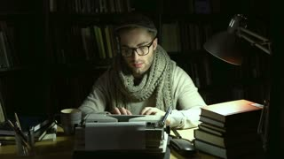 Writer typing his piece of art, crumpling and wasting a sheet of paper dissatisfied with result