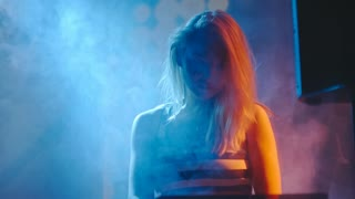 Young blond woman dancing behind DJ mixer console in dark smoky nightclub