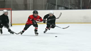 Young boys playing hockey on ice rink: one of them handling puck and his opponent chasing him and trying to get the puck in slow motion. Filmed with Sony Nex 700
