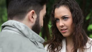 Young man explaining to his girlfriend why they can't be together pissing her off