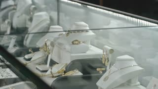 Young pretty lady looking at glass display in jewelry store and smiling
