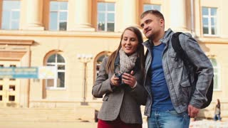 Young tourist couple happy about visiting new city: man embracing his girlfriend while she photographing famous places