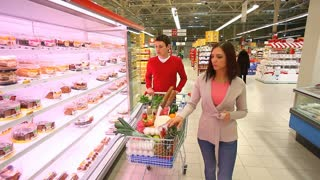 Young woman taking products from the shelves and putting them into cart pushed by guy