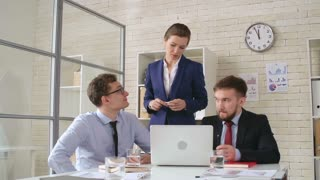 Zoom in of experienced businesswoman talking to young employees while working on laptop in office