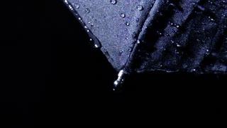 Raindrops falling on black umbrella in slow motion