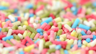 Sprinkles in a variety of color in close-up with slow panning sliding motion. Sweet colorful dessert topping.