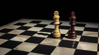 Two chess kings in battle. White king falls and match ends with checkmate.