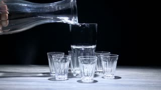 Water pouring in big glass with empty small glasses around.