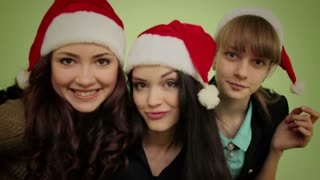 Group of girls in Christmas hats look at you