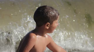 boy sitting on the beach and laugh