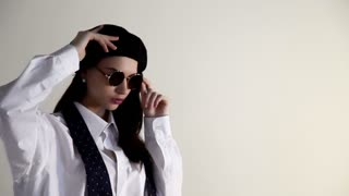 A Young woman in shirt take off the sunglasses and beret