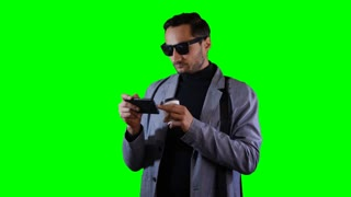Man in suit and black sunglasses type a message on mobile and hold coffee cup. Green screen, footage