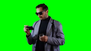 Man in suit and black sunglasses use mobile and hold coffee cup. Green screen, footage.