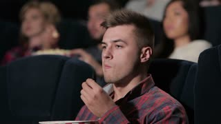 A male disappointed in a movie theater