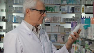 Aged male pharmacist taking off his glasses at the drugstore. Senior man in medical uniform holding bottle of some pharmacological drugs. Gray male druggist turning his face to the camera