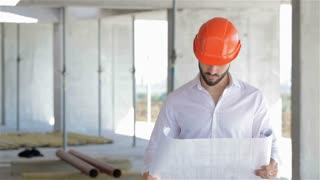Architector looks at the plan of the building under construction