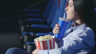 Asian girl in profile drinking soda in a cinema