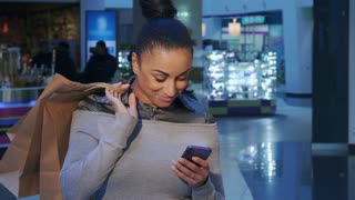 Attractive african american woman calling on the phone at the shopping. Pretty brunette female shopper holding smartphone in her hand. Close up of beautiful young girl standing with cellphone and