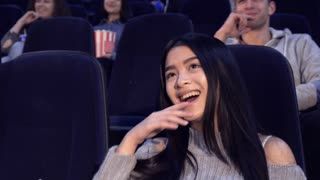 Attractive asian woman watching comedy at the movie theater. Close up of pretty brunette girl laughing at the cinema. Female teenager enjoying funny moments of the film