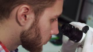 Attractive brunette man in white coat looking into the eyepieces of the scope. Bearded male scientist using microscope at the laboratory. Close up of young caucasian guy working on lab equipment