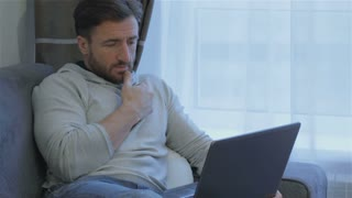 Attractive brunette man looking at the laptop screen at home. Middle aged bearded man touching his chin by his hand while looking at laptop screen. Handsome caucasian man using laptop touchpad