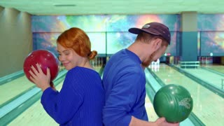 Attractive caucasian boy and girl dancing with bowling balls. Nice young couple standing back to back against background of lanes. Bearded guy in cap and redhead lady in blue sweater raising their