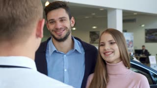 Attractive caucasian couple buying the car at the dealership. Pretty brown haired girl taking car key from the hand of salesman. Blond sales manager standing backwards against background of brunette