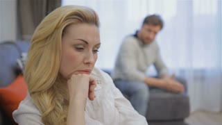 Attractive caucasian couple having conflict at home. Close up of sad pretty blond woman against background of offended brunette man. Pretty young woman holding her hand on her face while bearded man