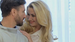 Attractive caucasian couple looking at each other at home. Close up of couple facing each other. Pretty blond woman holding her hands on the man's shoulders
