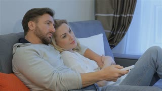 Attractive caucasian couple watching TV at home. Lovely couple lying embracing on the couch. Pretty blond woman lying on the man's shoulder