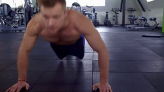Attractive caucasian sportsman training his chest muscles at the gym. Close up of strong male athlete doing push ups at the fitness center. Camera sliding from right to the left along fit man