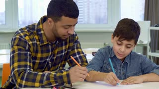 Attractive father and son drawing together at the table. Little brunette boy showing his parent what he drawn. Young african american man taking pencil from the desk