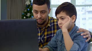 Attractive father and son waving at the laptop. Young african american man and his child chatting on video against background of christmas tree. Close up of little brunette boy sitting at the computer
