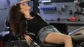 Attractive female biker lying back on the motorcycle seat. Sexy caucasian woman holding her hand on her curly hair at the mototrcycle workshop. Pretty slim girl looking into the camera while lying on