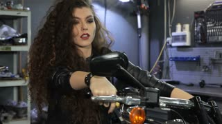 Attractive female biker shaking her hair on the motorcycle. Sexy young woman with dirty cheek holding her hands on the handlebar of the chopper. Pretty caucasian woman leaning back her head at the