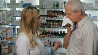 Attractive female pharmacist offering lozenges for cough to the senior male customer. Pretty blond woman in medical uniform giving blister with lozenges to the aged caucasian man. Young female