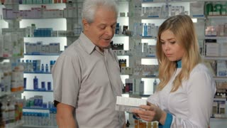 Attractive female pharmacist telling male customer about some medicine. Pretty blond woman in medical uniform holding box of drugs at the drugstore. Senior male client asking young female druggist